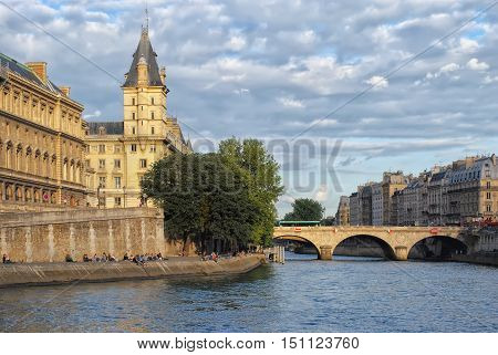 PARIS, FRANCE - June 22: the Parisians and visitors of city resting on a hot sunny day on the embankment Seine River June 22, 2012 in Paris. Part of the embankment the River Seine between the Louvre and Notre Dame de Paris.