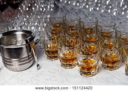 Glasses with whiskey and ice bucket closeup on party table