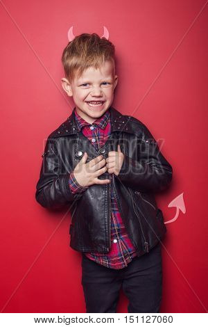 Little handsome devil with horns and tail. Kid. Halloween. Studio portrait isolated over red background