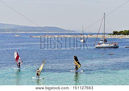 BOL, ISLAND BRAC, CROATIA - AUGUST 14, 2011: Surfing school at Zlatni Rat, famous turquoise beach in Bol on Brac island Dalmatia Croatia