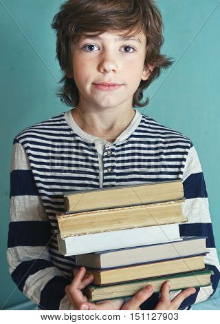 preteen handsome boy with book pile close up photo
