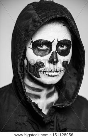 Portrait of woman painted like a skeleton for Halloween. Monochrome. Monochrome