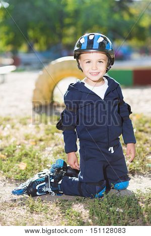 Smiling little skater boy posing on the knee pads