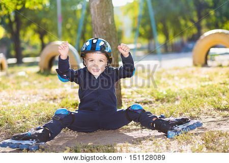 Cheerful skater boy in helmet sitting under the tree