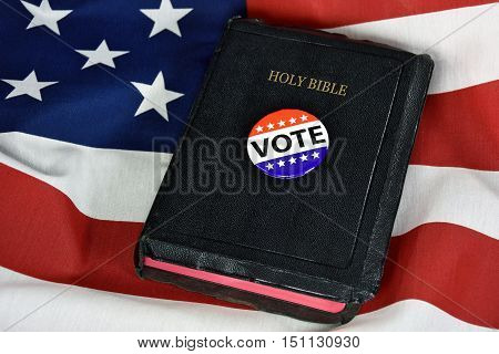 voting button and black Holy Bible on American flag