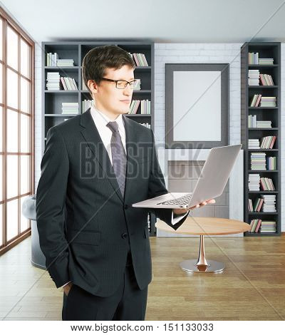 Businessman using laptop in luxurious library interior with blank picture frame. 3D Rendering