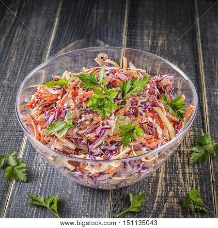 Homemade coleslaw in bowl on dark wooden background selective focus.