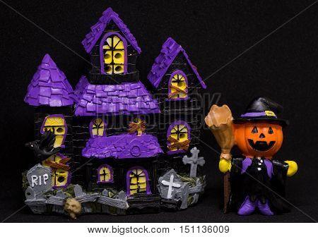 Halloween pumpkins ghost house doll on black background