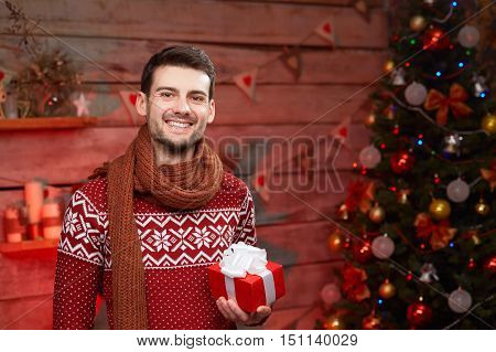 Happy young man holding present in christmas time. smiling Male wearing winter sweater with red gift box