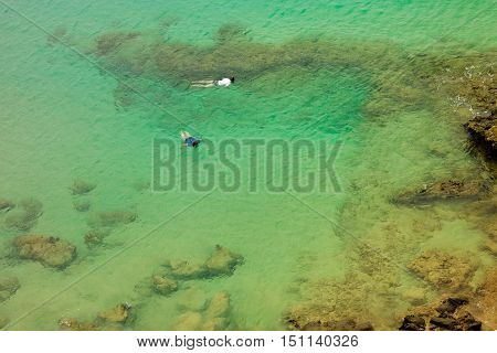 Two persons snorkeling in the sea with emerals transparent water cosed to the rocks.