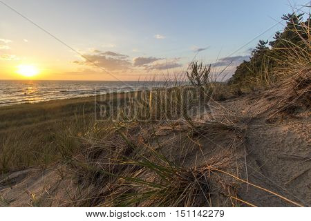Summer Beach Sunset Horizon. Sunset on the horizon of a wide sandy beach with a sand dune and dune grass in the foreground. Hoffmaster State Park. Michigan.