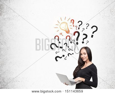 Smiling girl with laptop is standing near concrete wall with light bulb and question marks on it. Concept of idea. Mock up
