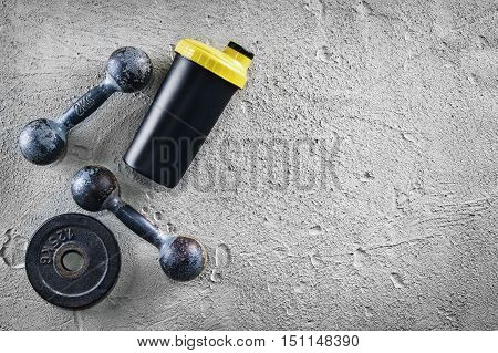 Fitness or bodybuilding concept background. Product photograph of old iron dumbbells and shaker on grey, conrete floor in the gym. Photograph taken from above, top view with lots of copy space