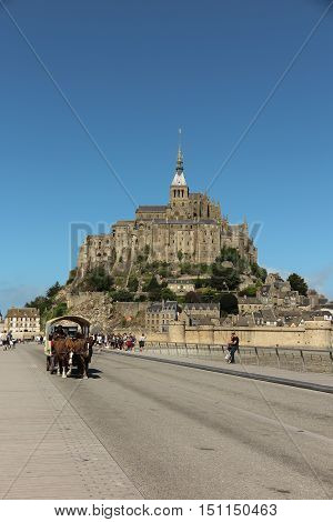 Mont Saint Michel France - September 8 2016: Panoramic view of famous Le Mont Saint-Michel tidal island on a sunny day with blue sky and clouds Normandy northern France