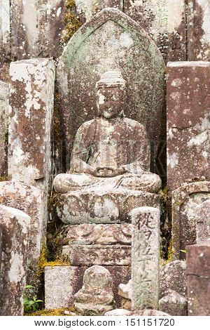 Kyoto Japan - September 15 2016: Weather took a heavy toll on the statue of the meditating or Amithabha Buddha at the cemetery of the Shinnyo-do Buddhist Temple.