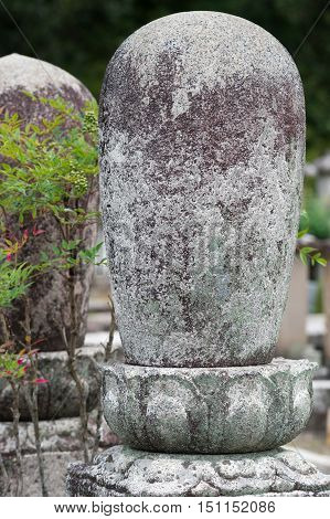 Kyoto Japan - September 15 2016: Weather took a heavy toll on the statue of cocoon-like white rock at the cemetery of the Shinnyo-do Buddhist Temple. Stands in lotus not unlike a Shivalingam.