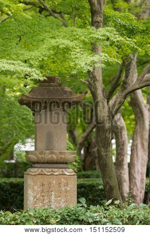 Kyoto Japan - September 15 2016: At the Shinnyo-do Buddhist Temple the stone statue of a lantern stands in the garden surrounded by green trees.