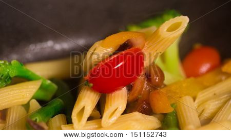 Primavera Pasta with mushrooms cooking in a pan closeup