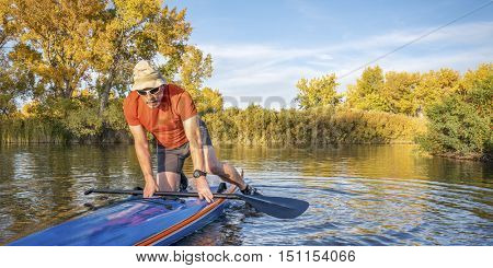 Senior male paddler is starting  workout on his racing stand up paddleboard in fall colors on lake in Colorado