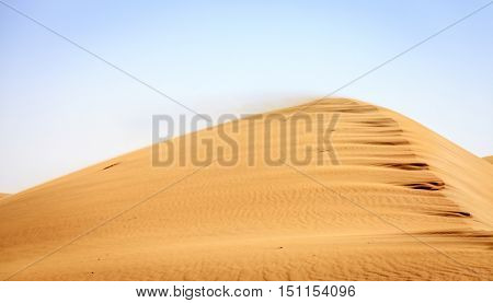 Wind blowing sand off the top of a dune in Desert Conservation Reserve near Dubai, UAE