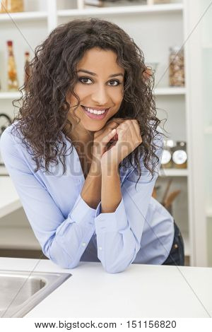 A beautiful happy young woman or girl wearing with perfect teeth and smile relaxing in her kitchen at home