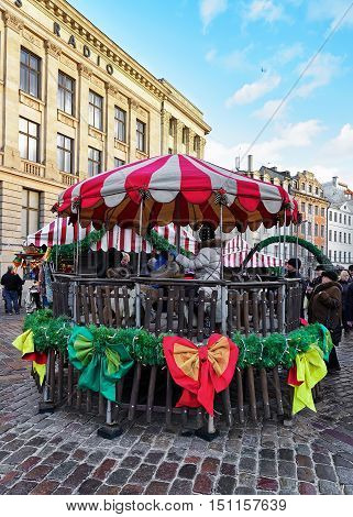 People At Carousel At Riga Christmas Market Of Dome Square
