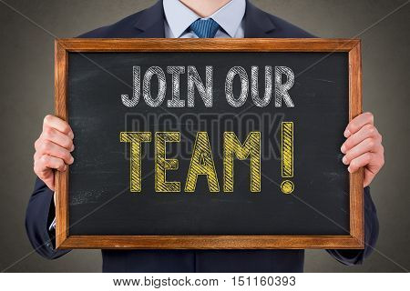 Businessman Writing Join Our Team on Blackboard Background