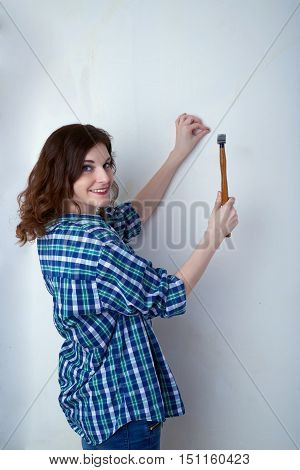 Smiling young woman in casual clothes in front of white unpainted wall working with hammer, happy people and construction concept