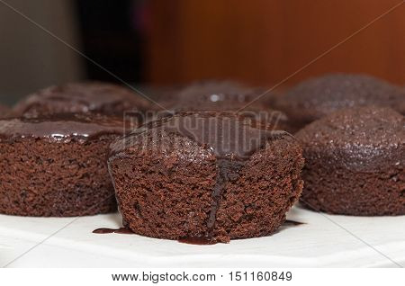 Small chocolate cakes with dripping chocolate icing on top. Homemade cakes made in round shape in a row.