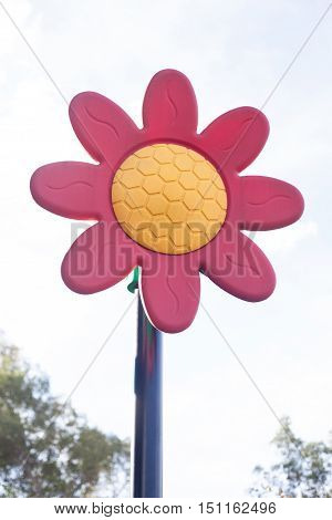 Artificial red and orange flower with bright sky behind