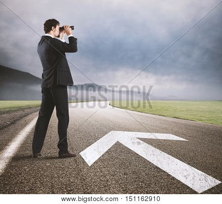 Businessman looks at the business future with binoculars on the road with arrow