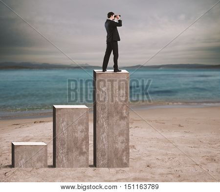 Businessman looks at the economic future with binoculars over a statistic
