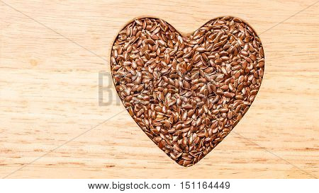 Diet healthcare healthy food. Raw flax seeds linseed heart shaped on wooden board background.