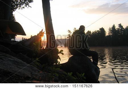 Silhouette of man sitting on rocks by a lake.