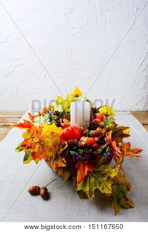 Thanksgiving decoration with silk fall leaves on linen napkin vertical. Thanksgiving greeting with fall decor. Fall centerpiece. Thanksgiving background. Copy space.