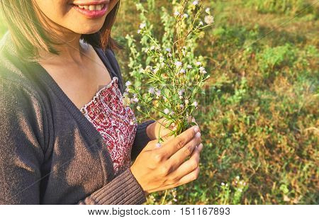 Asian beautiful woman is smiling and holding the tiny flowers in her hand.