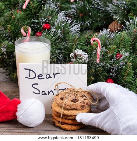 Stack of fresh cookies glass of milk and letter for Santa with hand wearing white glove reaching for a cookie.