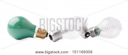 Green color bulb lying next to couple of transparent bulbs over white isolated background