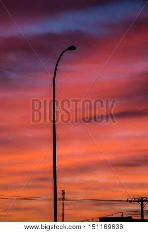 Street lamp post and sun rising colored clouds in the background