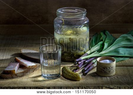 Vodka in glass and salted cucumbers and wild onion