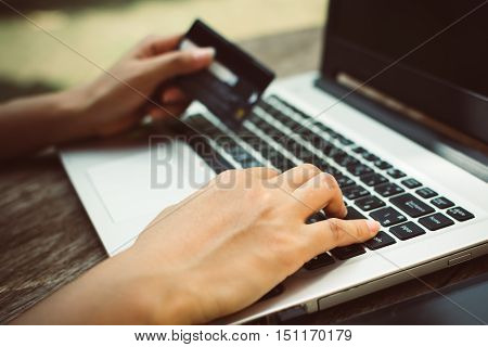 Woman Hands holding credit card and using laptop on wooden table. Online shopping
