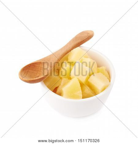 Pile of canned pineapple  in bowl with wooden spoon over isolated white background