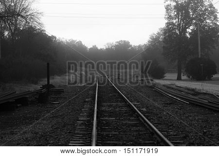 Black and white photo of train tracks on a foggy morning.