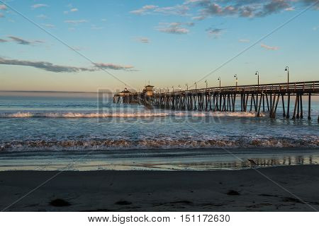 Imperial Beach fishing pier at dawn with beach in foreground in San Diego, California.