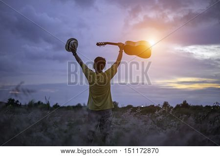 Man happy with guitar in meadow. travel and sunset soft and select focus