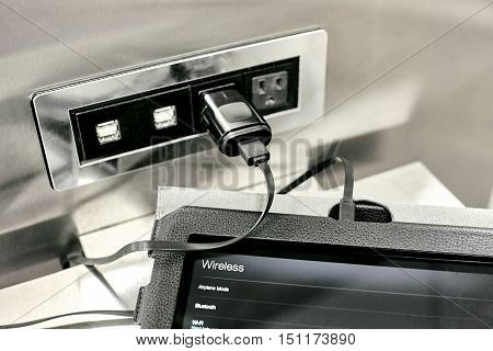 Charging Station with two USB plugs and two electrical plugs with a tablet pluggged into the electrical outlet and opened to wireless settings