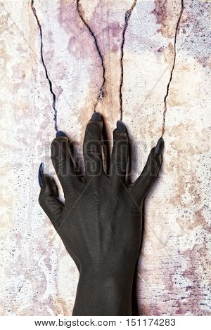 Black hands of the devil on wall background. Horror concept