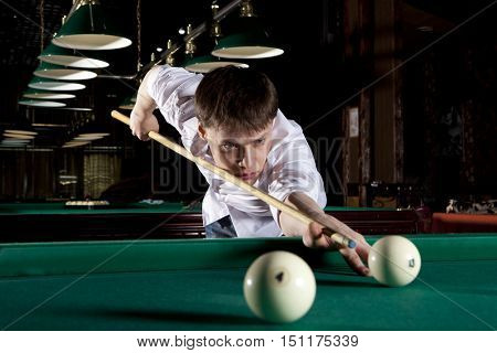 Young man playing billiards in the dark billiard club