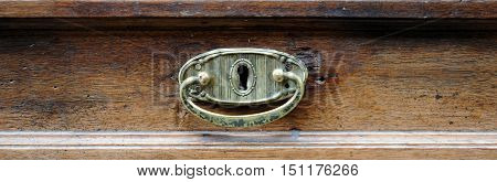 Brass handle of the drawer of an antique furniture.