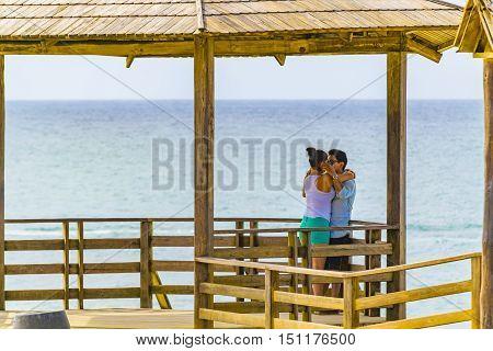 SALINAS, ECUADOR, OCTOBER - 2015 - Young couple kissing at La chocolatera a famous nature viewpoint towars the pacific ocean located at rocky coast in Salinas Ecuador